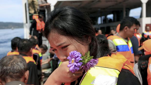 A relative weeps during a prayer for the victims of the ferry that sank on June 18, on a ship on Lake Toba, North Sumatra, Indonesia (Hendra Syamhari/AP)