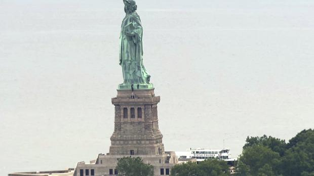 People climbing on the side of the Statue of Liberty's pedestal (AP)