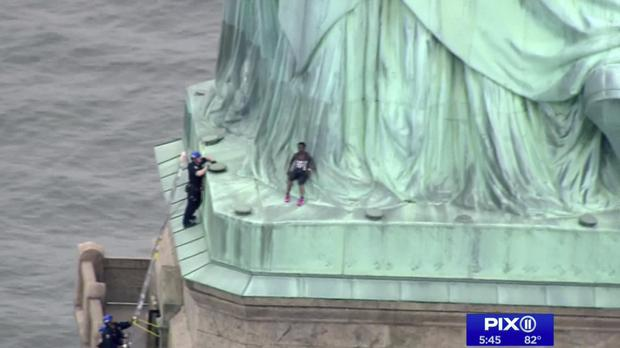 Police officers climbed up on a ladder to stand on a ledge nearby to talk the climber into descending (PIX11/AP)