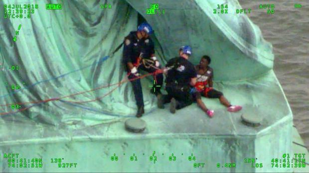Members of the NYPD Emergency Service Unit work to safely remove Therese Okoumou, a protester who climbed onto the Statue of Liberty (AP)