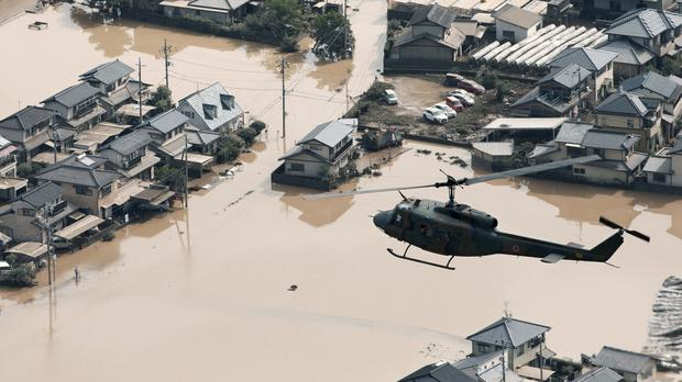 A helicopter flies over a flooded housing area in Kurashiki, Okayama prefecture, western Japan (Kyodo News/AP)