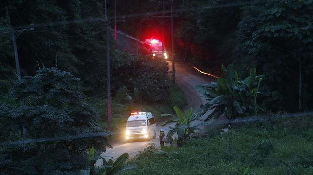 Two ambulances with flashing lights leaves the cave rescue area on Monday (Sakchai Lalit/AP)