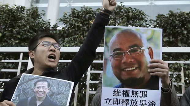 Pro-democracy activists hold pictures of Chinese activists Qin Yongmin last December (AP)