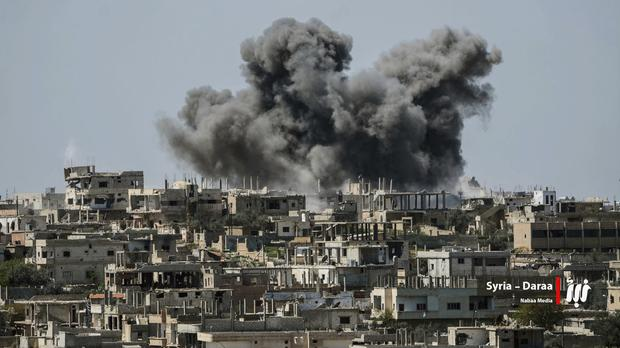 Smoke rises over buildings in Daraa province (Nabaa Media via AP)