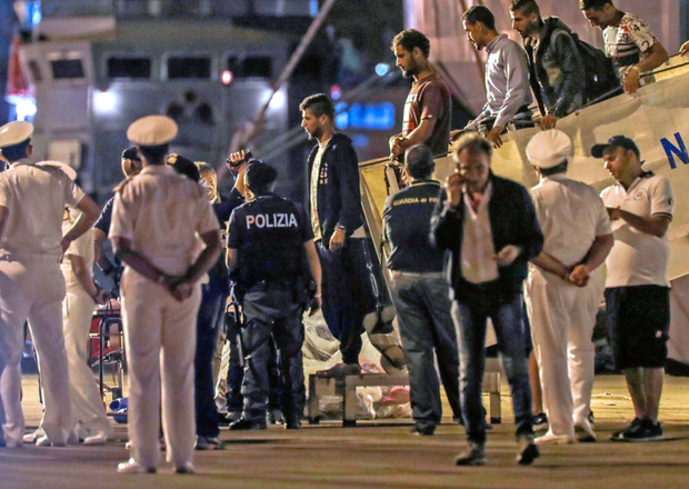 Some of the 67 migrants rescued at sea disembark from the Italian coast guard ship. Photo: AP