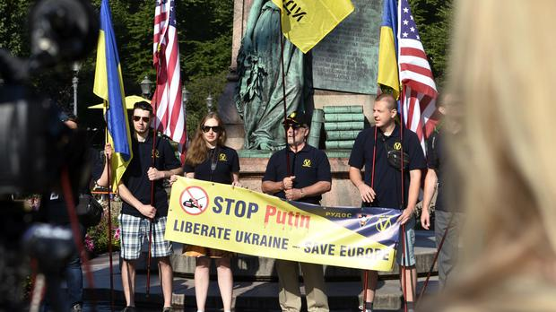 Demonstrators hold a sign 'Stop Putin, Liberate Ukraine – Save Europe' in Helsinki (AP)