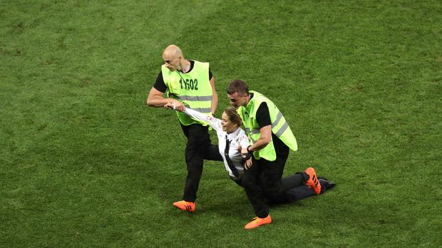 A protester is removed from the pitch during the World Cup final (Aaron Chown/PA)