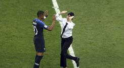 A woman who invaded the pitch in a protest claimed by Pussy Riot approaches France's Kylian Mbappe during the World Cup final (Thanassis Stavrakis/AP)