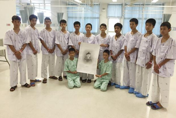 The rescued players pose with a sketch of the Thai navy diver who died while trying to rescue them (Ministry of Health/Chiang Rai Prachanukroh Hospital/AP)