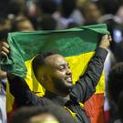 A Ethiopian holding an Ethiopian flag waves at the Eritrean president in Addis Ababa (AP)