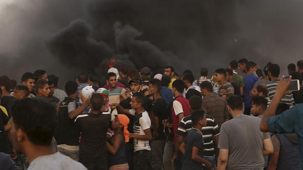 Protesters gather while burning tyres near the Gaza Strip's border with Israel (Adel Hana/AP)