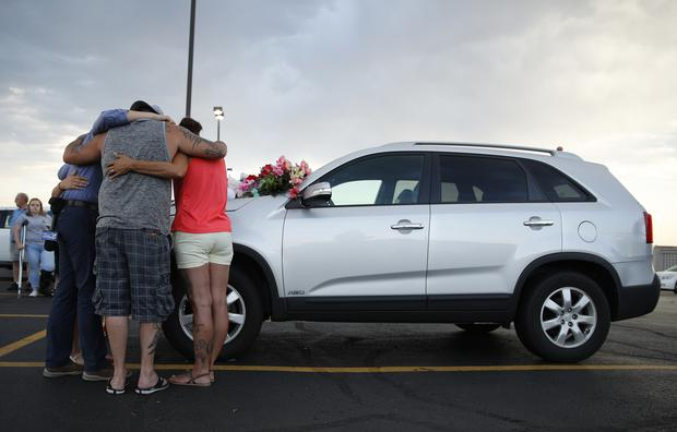 People pray by a car thought to belong to a victim of the accident (AP)