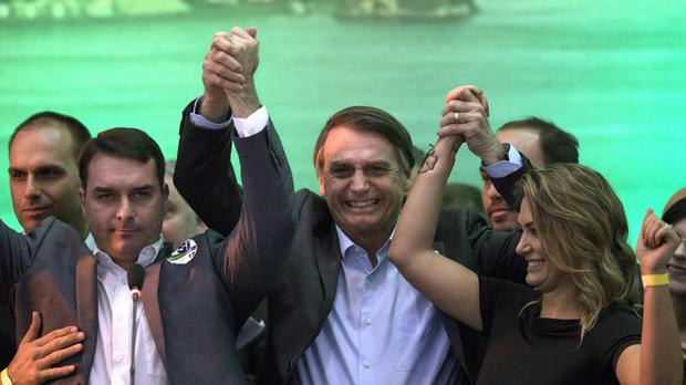 Brazil's presidential candidate Jair Bolsonaro holds ups his hands with his wife Michelle and son Flavio (Leo Correa/AP)