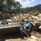 Local residents walk on boulders and debris left by a flash flood in Yen Bai province (AP)