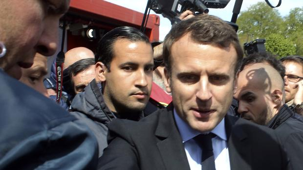 Alexandre Benalla, pictured here over the shoulder of Emmanuel Macron (AP)