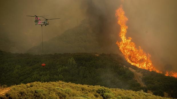 A helicopter carries water while battling the River Fire burning in Lakeport, California (Noah Berger/AP)
