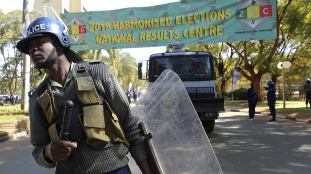 A police officer patrols outside the Election Results Centre at a local hotel in Harare (Tsvangirayi Mukwazhi/AP)