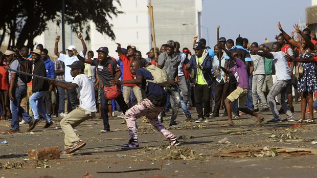 Opposition party supporters react after police fired tear gas, in Harare (Tsvangirayi Mukwazhi/AP)