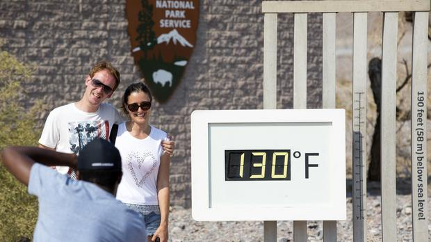 A couple poses at a thermometer in Death Valley National Park, California on July 26 (Richard Brian/Las Vegas Review-Journal/PA)