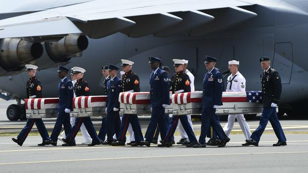 Military members carry transfer cases from a C-17 at a ceremony marking the arrival of the presumed US war dead (AP Photo/Susan Walsh)