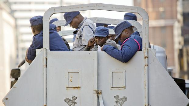 Zimbabwean police officers are stationed outside the MDC opposition party headquarters in Harare (Jerome Delay/AP)