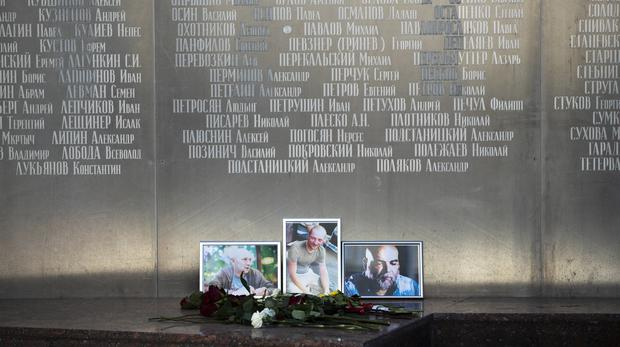 Flowers are placed by portraits of slain journalists Alexander Rastorguyev, Kirill Radchenko and Orkhan Dzhemal, at the Russian journalists Union building in Moscow (AP)