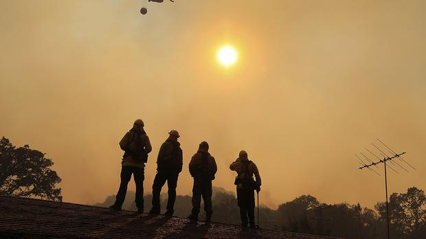 Firefighters stand watch on a roof as a wildfire sweeps through the area near Lakeport (Kent Porter/AP)