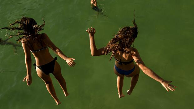 Two women jump from a platform over the water at La Concha beach in San Sebastian, Spain (AP)