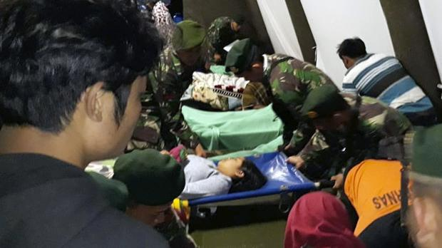 Indonesian soldiers tend to a woman injured in the earthquake (AP)