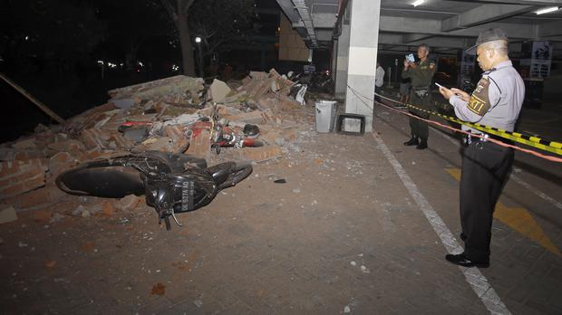 Police at the scene of debris on top of a motorcycle after an earthquake in Bali (Firdia Lisnawati/AP)