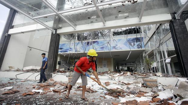 Workers clean up the debris at a building damaged by the earthquake (Firdia Lisnawati/AP)