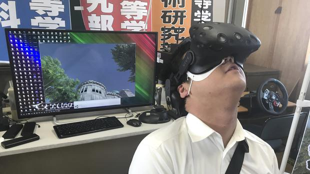 Namio Matsura, a 17-year-old member of the computation skill research club at the Fukuyama Technical High School, watches Hiroshima city before the atomic bomb falls in a virtual reality experience (Haruka Nuga/AP)
