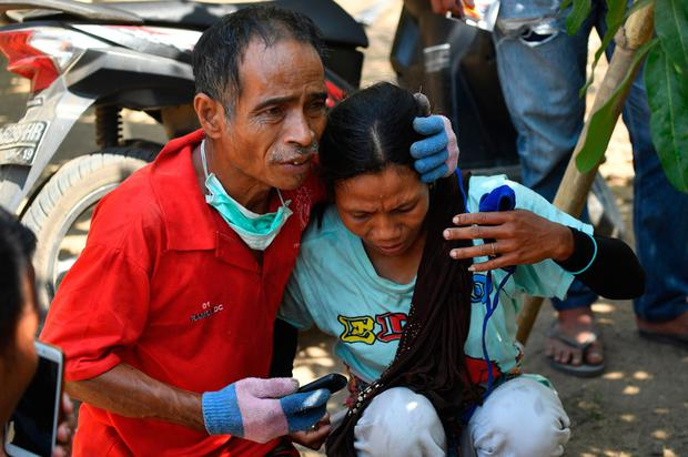 An emergency worker comforts a woman after the latest tremor
