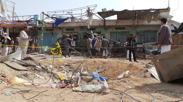People gather at the site of the air strike in Saada, Yemen (AP Photo/Kareem al-Mrrany)