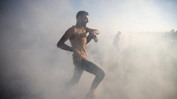 Palestinian protesters escape from teargas fired by Israeli troops during a protest at the Gaza Strip's border with Israel (Khalil Hamra/AP)