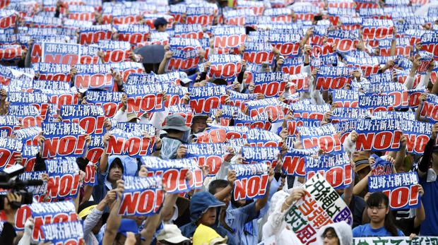 Protesters display signs against a planned US military base relocation (Koji Harada/Kyodo News/AP)