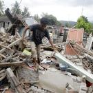 A man walks through debris from Sunday's earthquake in West Lombok, Indonesia (Firdia Lisnawati/AP)
