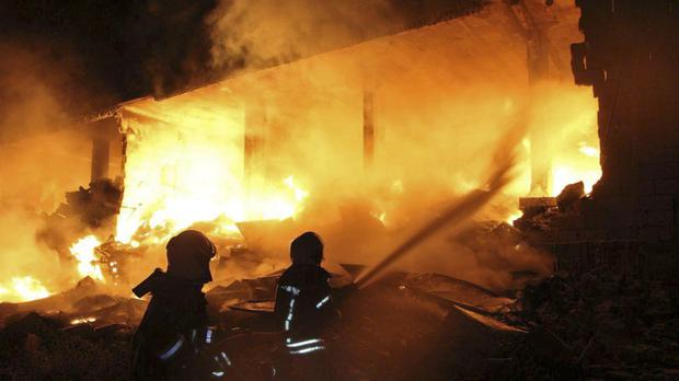 A fire at the scene of an explosion that hit a five-story building (Syrian Civil Defence/AP)