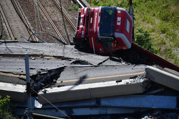 A truck lies on a side over the rubble of the collapsed bridge (AP)