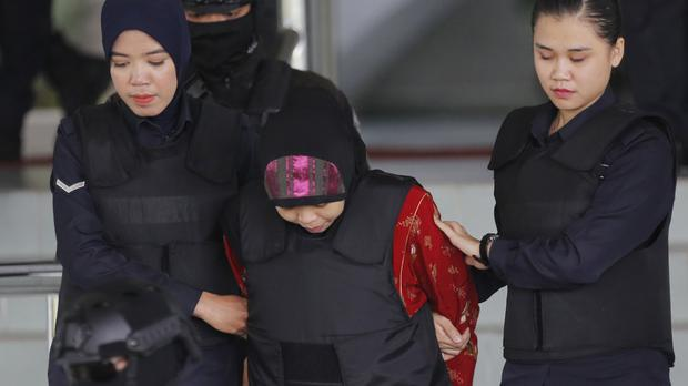 Indonesian Siti Aisyah, centre, is escorted by police as she leaves the court hearing (Yam G-Jun/AP)