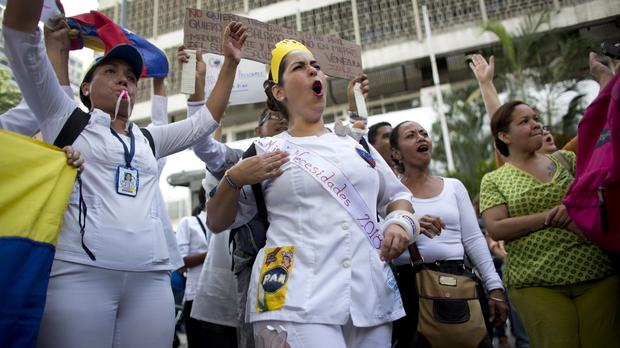 Nurse Monica Arangure, centre, wears a crown and a band that in Spanish says My needs during a protest demanding higher, fair wages and against the government of President Nicolas Maduro (Ariana Cubillos/AP)