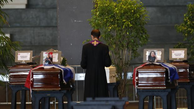 A priest stands by the coffins of victims of the Genoa bridge collapse (Antonio Calanni/AP)