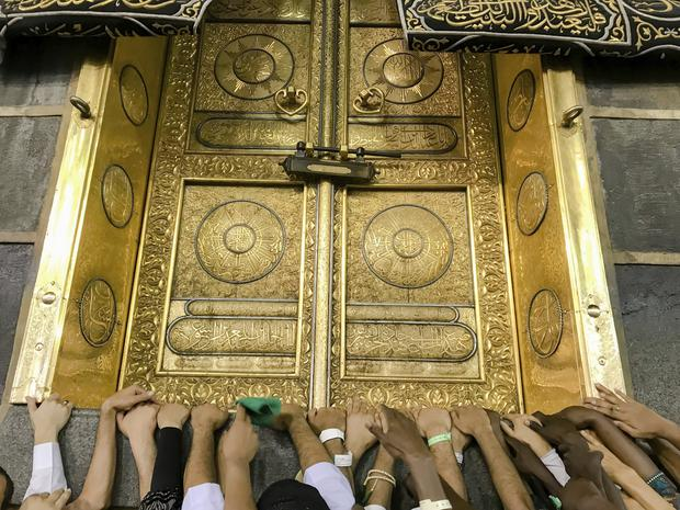 Muslim pilgrims touch the golden door of the Kaaba (Dar Yasin/AP)