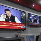 People watch a televised address of Pakistan's newly elected prime minister Imran Khan (Fareed Khan/AP)
