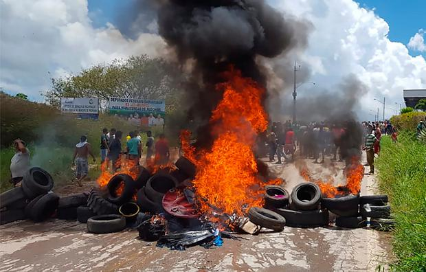 Residents of the Brazilian border town of Pacaraima burn tyres and belongings of Venezuelan immigrants after attacking their two main makeshift camps, leading them to cross the border back into their home country. Photo: Isac Dantes/AFP/Getty