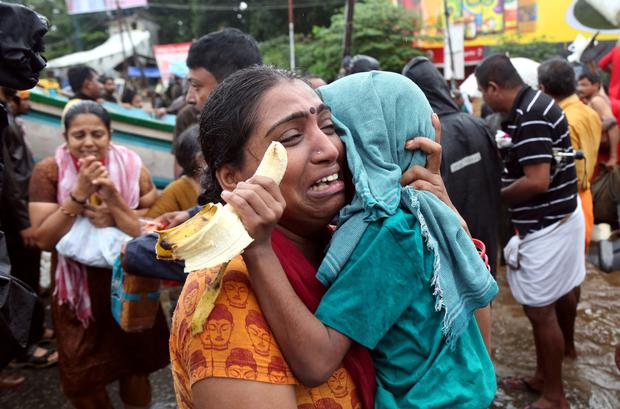 A woman cries as she holds her son after they were evacuated. REUTERS
