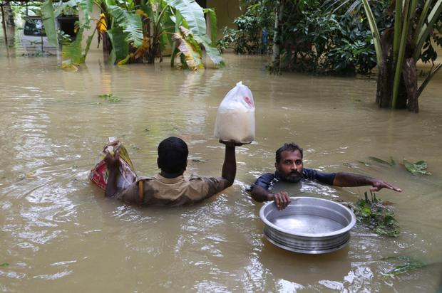 An Indian policeman, left, and a volunteer carry supplies for stranded people in a flooded area in Chengannur in the southern state of Kerala. (AP Photo/Aijaz Rahi)