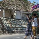 Indonesian men carry the body of a victim of last week's earthquake past a damaged building during a funeral on Lombok (AP Photo/Fauzy Chaniago)