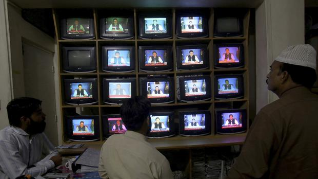 People watch a televised address of Pakistan's newly elected Prime Minister Imran Khan (AP)