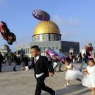 Palestinian children hold balloons on the first day of Eid al-Adha near the Dome of the Rock Mosque in the Al Aqsa Mosque compound in Jerusalem's old city (Mahmoud Illean/AP)